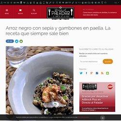 Arroz negro con sepia y gambones en paella. Receta de cocina elaborada y deliciosa.