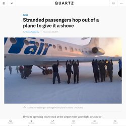 Stranded passengers hop out of a plane to give it a shove